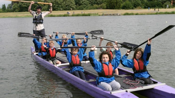 Bellboat Helm. A group of children in a bellboat waving their paddles and cheering