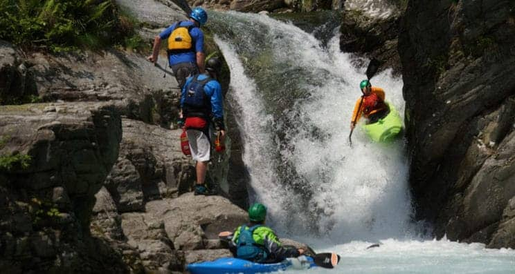 Advanced White Water Kayak leader. A kayak heads over a large falls whilst a leader looks on.