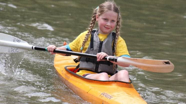Coaching young paddlers. A young girl heads out in a kayak.