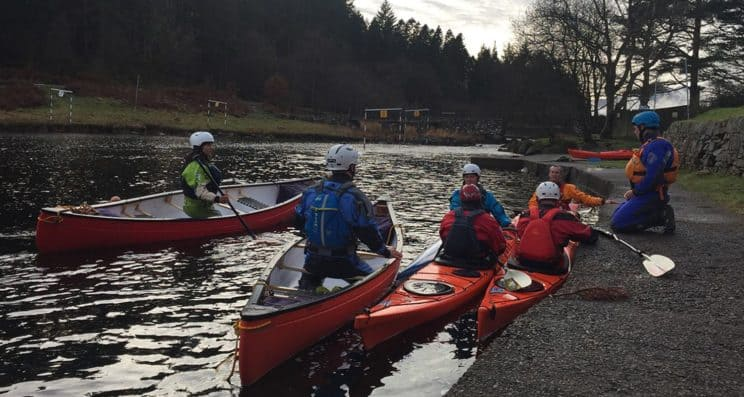 Foundation Safety and Rescue Training. A group in different crafts on the water whilst a tutor gives information from the bank.