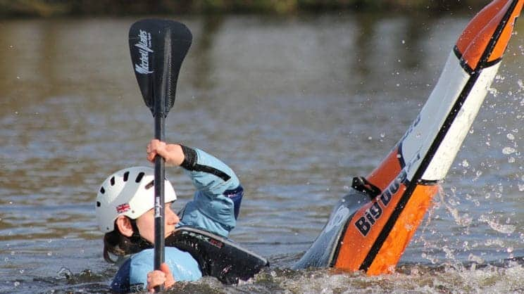 Fundamental Paddlesport Skills. A freestyle kayaker performs a move on the water.