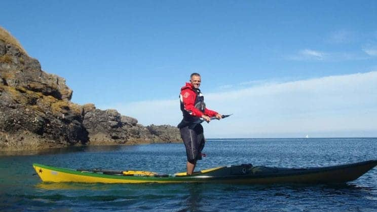 Fundamentals of Movement. A paddler stands up in a boat on the sea.