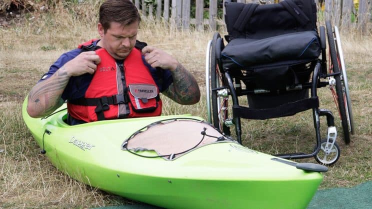 Intermediate Paddle-Ability. A paddler leaves his wheelchair behind and is sat in a kayak