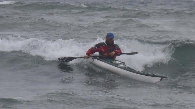 Sea Kayak Leader. A paddler navigating a moderate wave on the sea.
