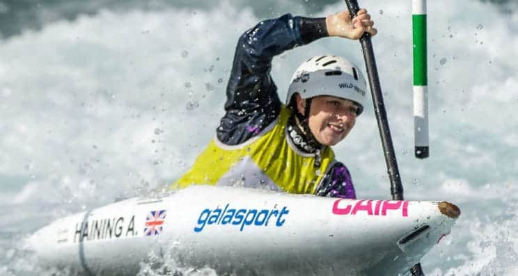 Slalom Support. A paddler heads down the water and navigates a green pole.