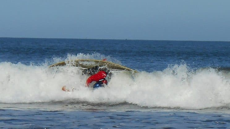 Surf Safety and Rescue. A surf kayaker being wiped out on a wave.