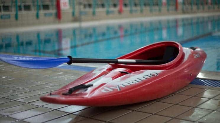 Swimming Pools. A kayak sits by a pool.