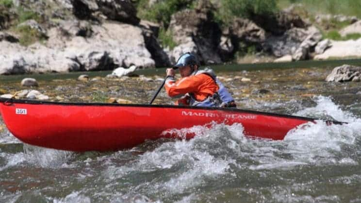 White Water OC1 Leader. A paddler in a red OC1 boat navigates moderate breaking water.