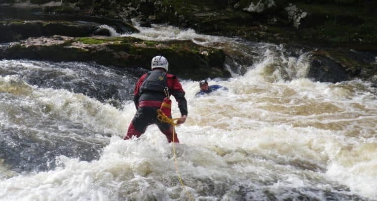 White Water Safety and Rescue. A paddler performing a rescue to another stuck in white water.